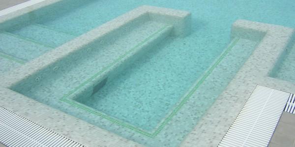 Piscina interrata in cemento armato e copertura in mosaico, con scale e seduta in acqua