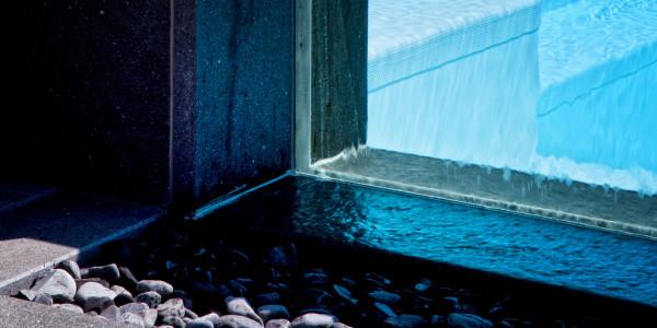 Piscina semi-interrata con Sfioro a cascata Crystal in metacrilato, con gradini e griglia a ghiaia.