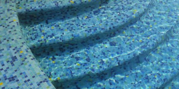 Piscina interrata con mosaico e scale.